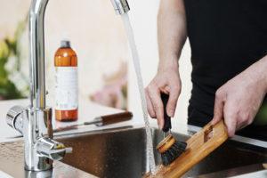 Ihminen tiskaa leikkuulautaa juoksevan veden alla keittiöaltaassa.