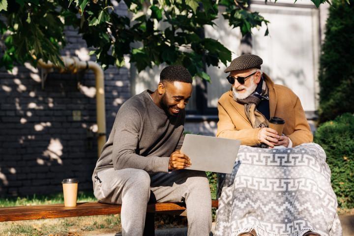Nuorempi ja vanhempi mies istuvat pihalla katsomassa nuoremman läppäriä