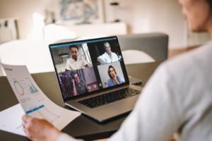 Etäkokousten viestintää voi tehostaa esittämällä tietoa kaaviona ja tiivistyksinä, kuten kuvan etäkokoukseen osallistuva nainen tietokoneellaan